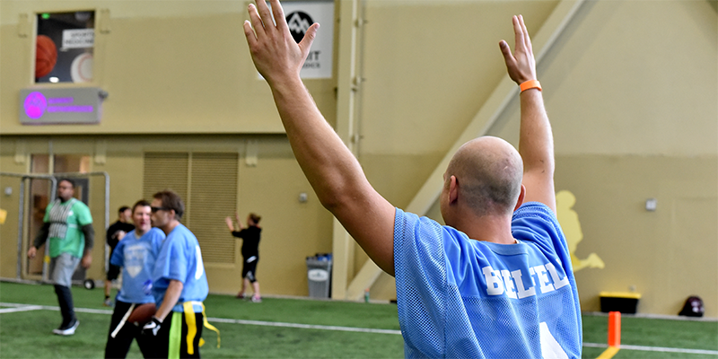 A Special Olympics Minnesota flag football athlete raises his arms over his head in victory