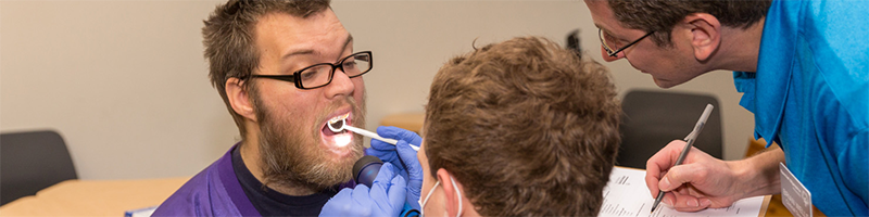 A dental technician examines a Special Olympics Minnesota athlete's teeth while a volunteer looks on