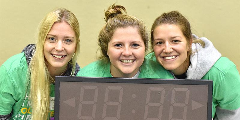 Three Special Olympics Minnesota flag football volunteers smile at the camera