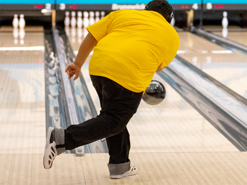 A Special Olympics Minnesota bowling athlete sends his ball down a lane