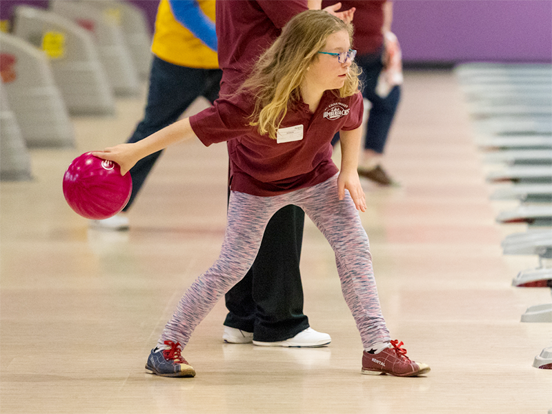 A Special Olympics Minnesota athlete aims her bowling ball