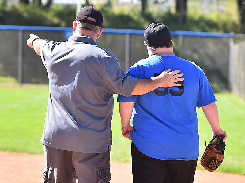 A Special Olympics Minnesota coach helps a softball athlete