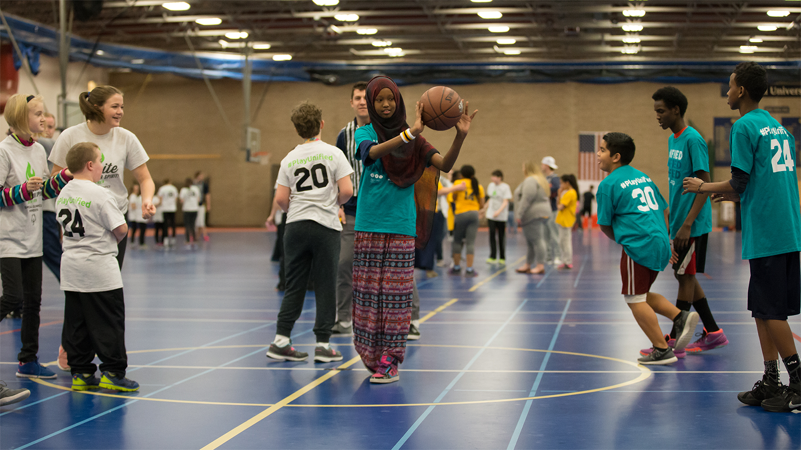 A Special Olympics Minnesota Unified basketball player passes the ball off to someone on her team while another team looks on