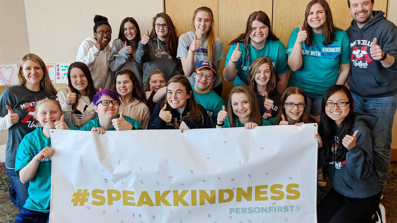 A group of Unified students smile and give the camera a thumbs-up while holding a #SpeakKindness Person First banner