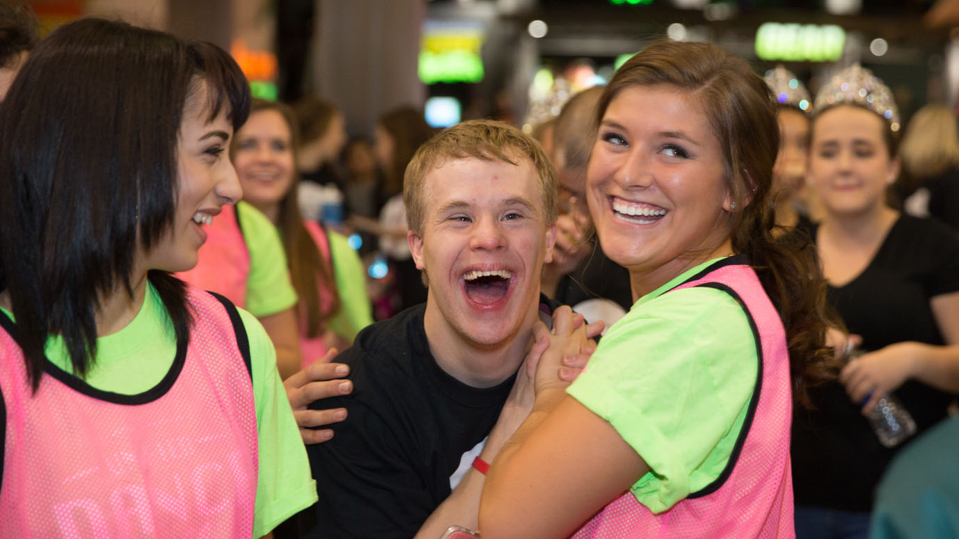 A Special Olympics Minnesota athlete hangs out with volunteers at the Unified Dance Marathon