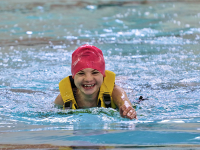 Smiling girl with life jacket and pink pool cap swimming in large swimming pool