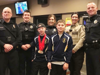 Five Prior Lake police officers and two Special Olympics Minnesota athletes pose at a Law Enforcement Torch Run Tip-A-Cop event